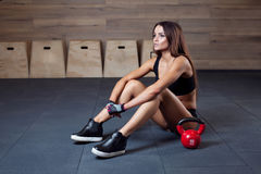 Giovane donna che la allunga indietro dopo un allenamento pesante del kettlebell Fotografie Stock Libere da Diritti