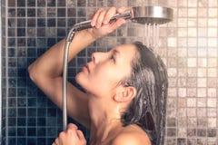 Giovane donna che lava i suoi capelli lunghi sotto la doccia Immagini Stock Libere da Diritti