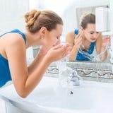 Giovane donna che lava il suo fronte Immagine Stock
