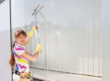 Giovane donna che lava la finestra Fotografie Stock