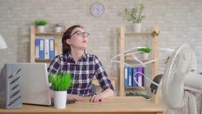 Giovane donna che lavora ad un computer portatile accanto alle fughe di un fan dal calore Mo lento stock footage