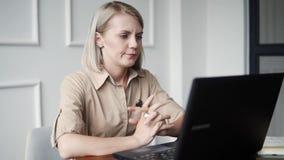 Giovane donna che lavora al caffè moderno che è ufficio per le free lance Lavoro duro alla moda della femmina adulta con i docume stock footage