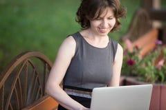 Giovane donna che lavora al computer portatile fuori Fotografie Stock