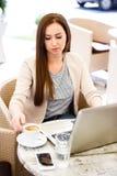 Giovane donna che lavora al computer portatile mentre sedersi all'aperto al caffè - Fotografia Stock Libera da Diritti