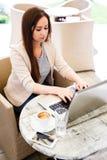 Giovane donna che lavora al computer portatile mentre sedersi all'aperto al caffè - Immagine Stock Libera da Diritti