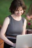 Giovane donna che lavora al computer portatile in parco Immagine Stock