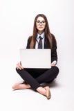 Giovane donna che lavora al suo computer portatile, sedentesi sul pavimento fotografie stock
