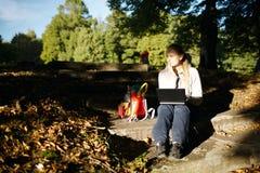Giovane donna che lavora all'aperto su un computer portatile Fotografie Stock Libere da Diritti