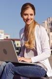 Giovane donna che lavora con il computer portatile Immagine Stock