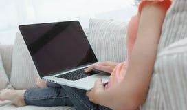 Giovane donna che lavora con il computer portatile che si siede sul sofà Fotografia Stock Libera da Diritti