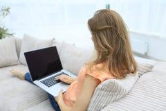 Giovane donna che lavora con il computer portatile che si siede sul sofà Immagine Stock Libera da Diritti
