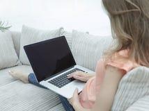 Giovane donna che lavora con il computer portatile che si siede sul sofà Immagini Stock Libere da Diritti