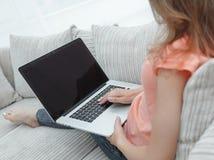 Giovane donna che lavora con il computer portatile che si siede sul sofà Fotografia Stock