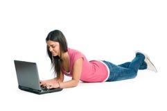 Giovane donna che lavora e che pratica il surfing sul computer portatile Immagine Stock