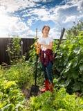 Giovane donna che lavora nel giardino del cortile al giorno soleggiato Fotografie Stock Libere da Diritti