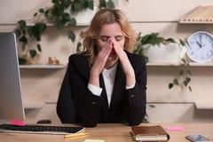 Giovane donna che lavora nell'ufficio, sedentesi allo scrittorio Fotografia Stock Libera da Diritti
