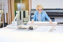 Giovane donna che lavora nella stamperia fotografia stock libera da diritti