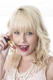 Giovane donna che lecca labbro che tiene rossetto rosso Immagini Stock Libere da Diritti