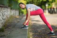 Giovane donna che lega i pizzi di scarpa da corsa in parco nel bello giorno di estate Immagine Stock