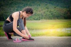 Giovane donna che lega le sue scarpe di sport sull'esercitazione della stuoia Concetto di Immagini Stock Libere da Diritti