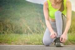 Giovane donna che lega le sue scarpe di sport sull'esercitazione della stuoia Concetto di Fotografia Stock Libera da Diritti