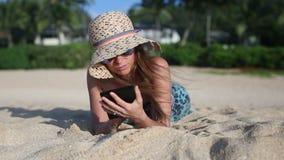 Giovane donna che legge il libro elettronico di A sulla spiaggia stock footage