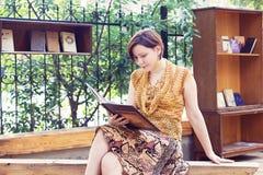 Giovane donna che legge il libro nel parco Fotografia Stock Libera da Diritti