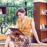 Giovane donna che legge il libro nel parco Immagini Stock Libere da Diritti