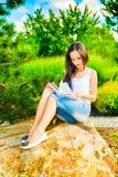 Giovane donna che legge un libro Immagini Stock