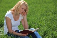 Giovane donna che legge un libro all'esterno Fotografie Stock