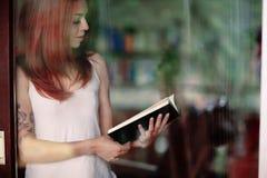 Giovane donna che legge un libro a casa davanti ad una finestra Immagine Stock
