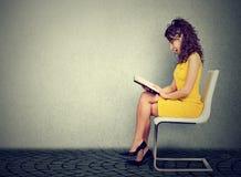 Giovane donna che legge un libro che si siede su una sedia Fotografia Stock Libera da Diritti