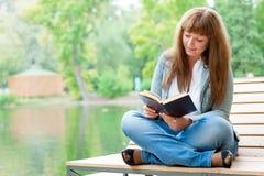 Giovane donna che legge un libro che si siede sul banco Fotografia Stock