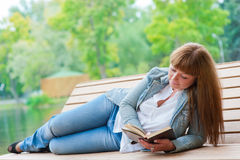 Giovane donna che legge un libro che si siede sul banco Fotografia Stock Libera da Diritti