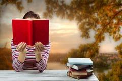 Giovane donna che legge un libro e che copre il suo fronte Immagine Stock