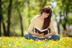 Donna che legge un libro nel parco con i fiori Immagine Stock