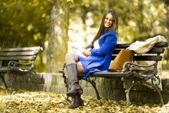 Giovane donna che legge un libro nella sosta Fotografia Stock