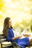 Giovane donna che legge un libro nella sosta Immagine Stock Libera da Diritti