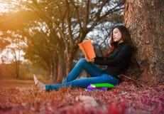 Giovane donna che legge un libro in sosta Fotografie Stock Libere da Diritti
