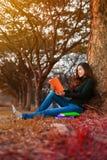Giovane donna che legge un libro in sosta Fotografie Stock