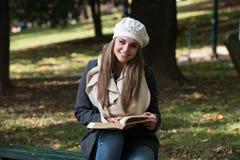 Giovane donna che legge un libro in sosta Immagini Stock