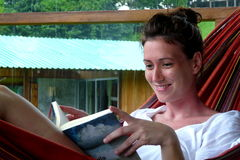 Giovane donna che legge un libro su un'amaca nella casetta di Fincas Maresia, Bahia Drake, parco nazionale di Corcovado, Costa Ri Fotografia Stock Libera da Diritti