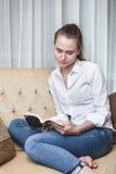 Giovane donna che legge un libro sul sofà Fotografia Stock