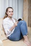 Giovane donna che legge un libro sul sofà Fotografia Stock Libera da Diritti