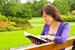 Giovane donna che legge un libro in una sosta Immagini Stock