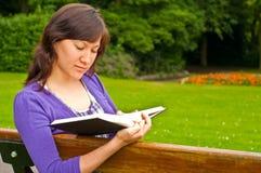 Giovane donna che legge un libro in una sosta Fotografia Stock