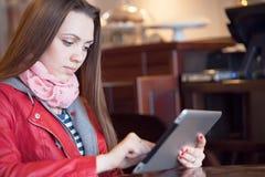 Giovane donna che legge una compressa digitale immagine stock libera da diritti