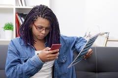 Giovane donna che manda un sms e che legge Fotografia Stock