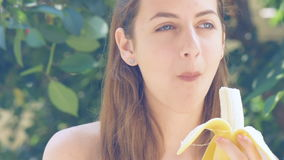 Giovane donna che mangia banana video d archivio