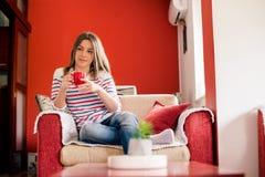 Giovane donna che mangia caffè Fotografia Stock
